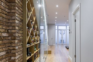 Basement entrance with custom made glass panelled wine cellar